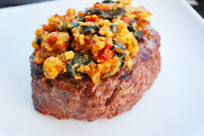 Grilled steak with a cooked blend of feta, spinach and sun-dried tomato pesto on top