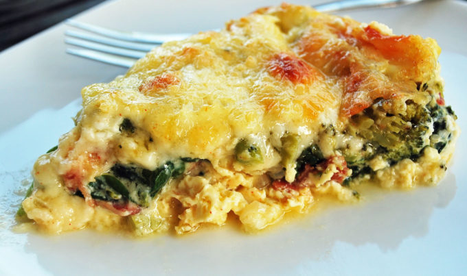 Favorite crustless quiche slice made with cheese, bacon, spinach, onions and broccoli