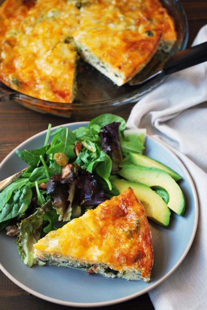 overhead shot of plate of quiche with salad and quiche in pan
