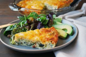 loaded quiche plated with salad and avocado