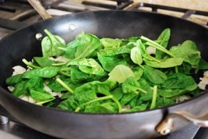 baby spinach cooking in pan for quiche
