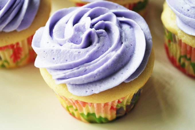 A close up of a lavender frosted cupcake