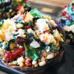 three portobello mushrooms in a pan baked and filled with a Mediterranean inspired stuffing