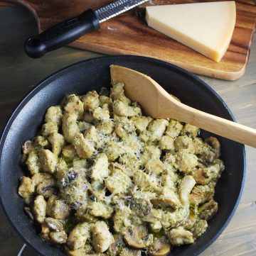 skillet of pesto chicken with block of parmesan cheese