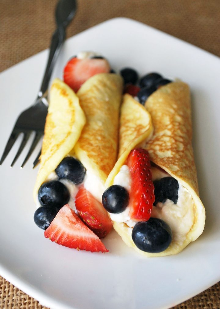 stuffed crepes on a white plate with strawberries and blueberries with fork