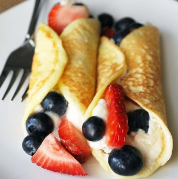 2 berry stuffed crepes on a plate with fork