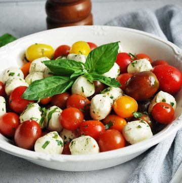 close up of caprese salad in a bowl with fresh basil