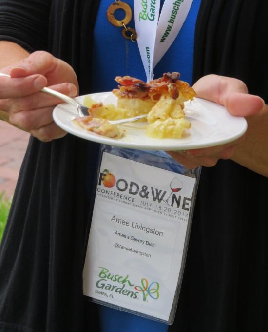A woman holding a plate of Potato Casserole