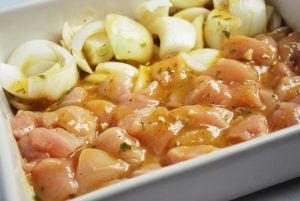 onions and chicken marinating in peach puree vinaigrette