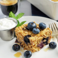Slice of blueberry baked oatmeal on a plate topped with fresh blueberries and a side of yogurt