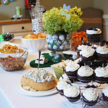Food spread on a dining room table for a gentlemen baby shower