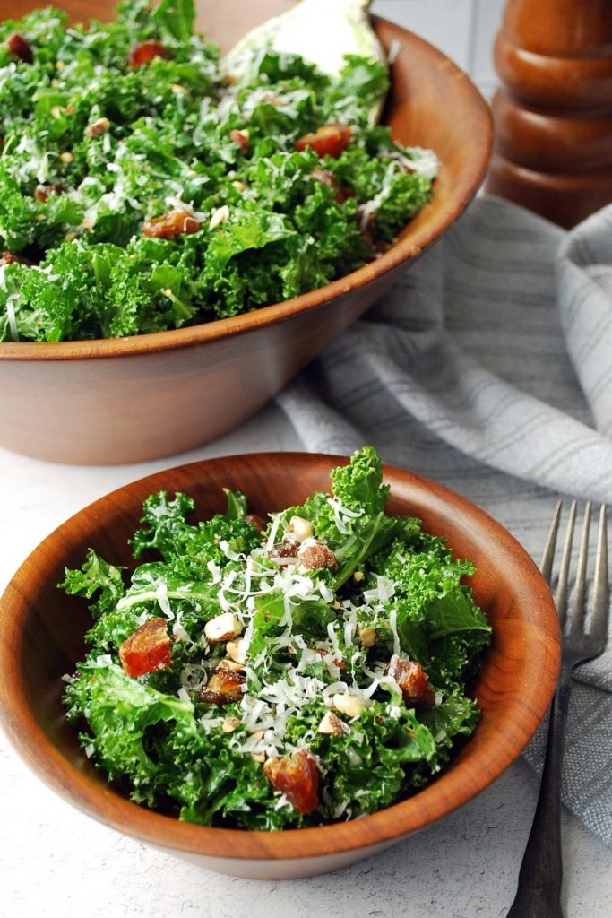 close up of kale salad in a small wood bowl with a serving bowl of salad and a peppermill in the background