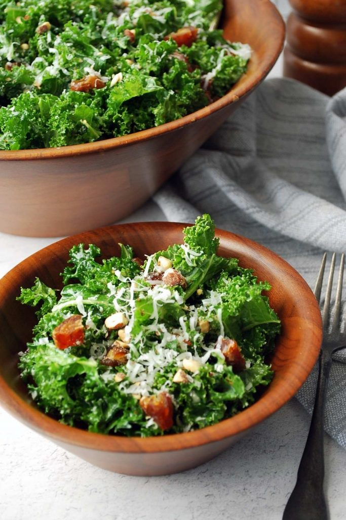 side view of a served bowl of kale salad with a large salad bowl filled with kale salad in the background