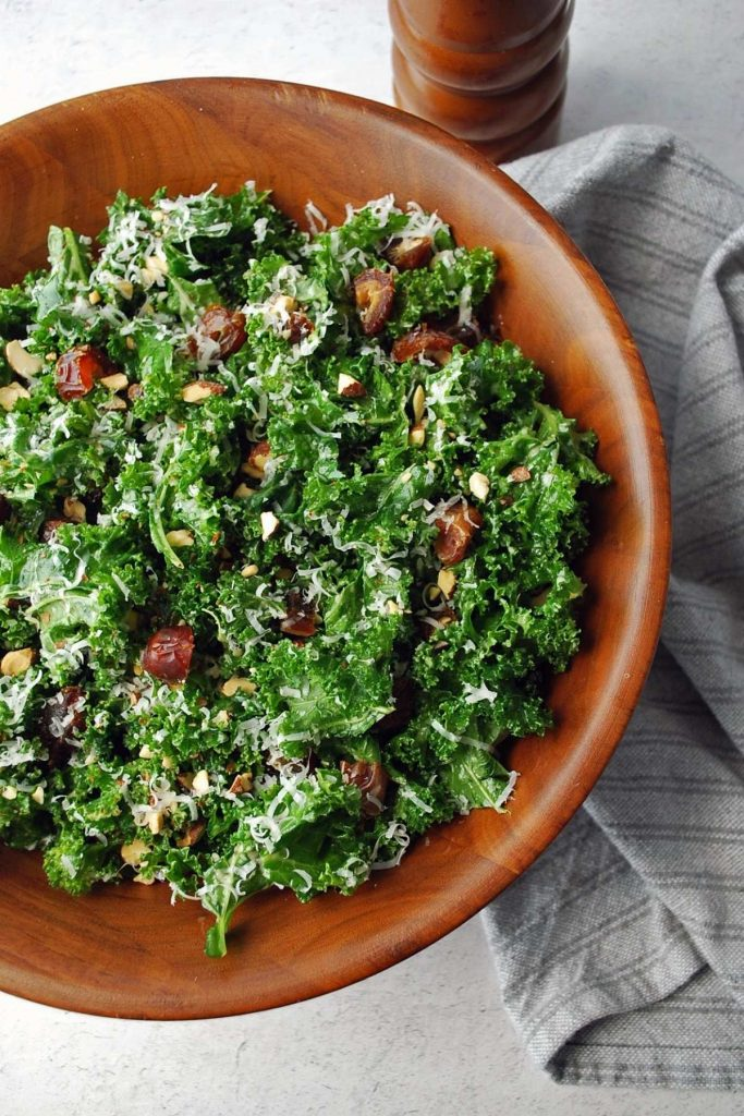 kale salad with dates and parmesan cheese in a large wooden salad bowl