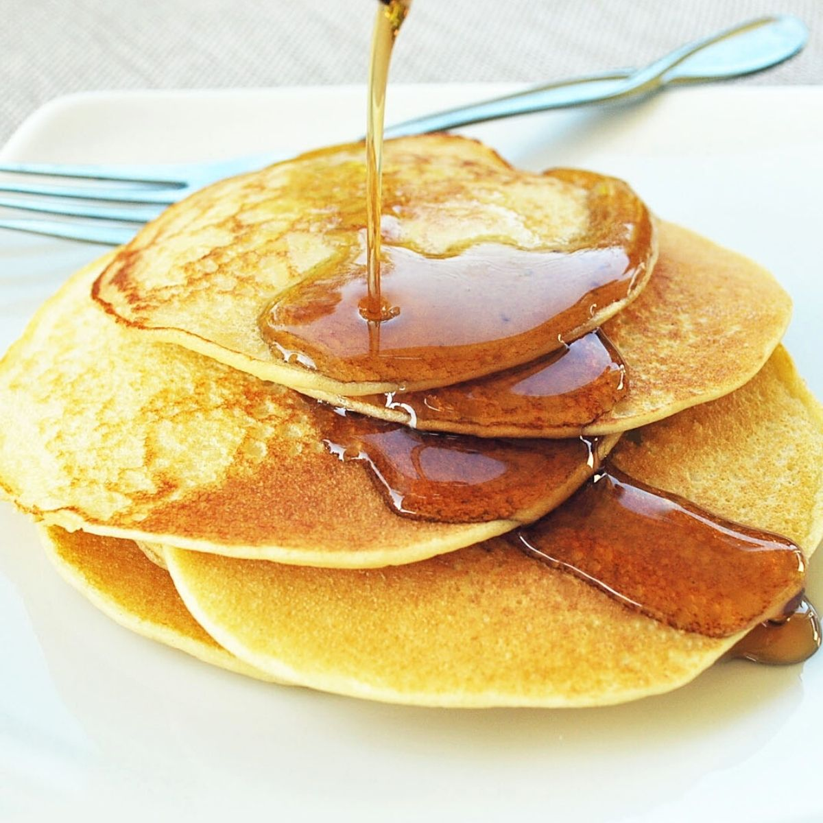 stack of ricotta cheese pancakes drizzled with maple syrup