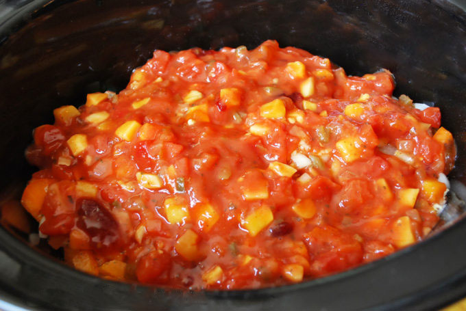 Salsa poured into slow cooker for mango salsa chicken