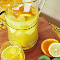 Pitcher of sangria with sliced citrus fruit and kiwi