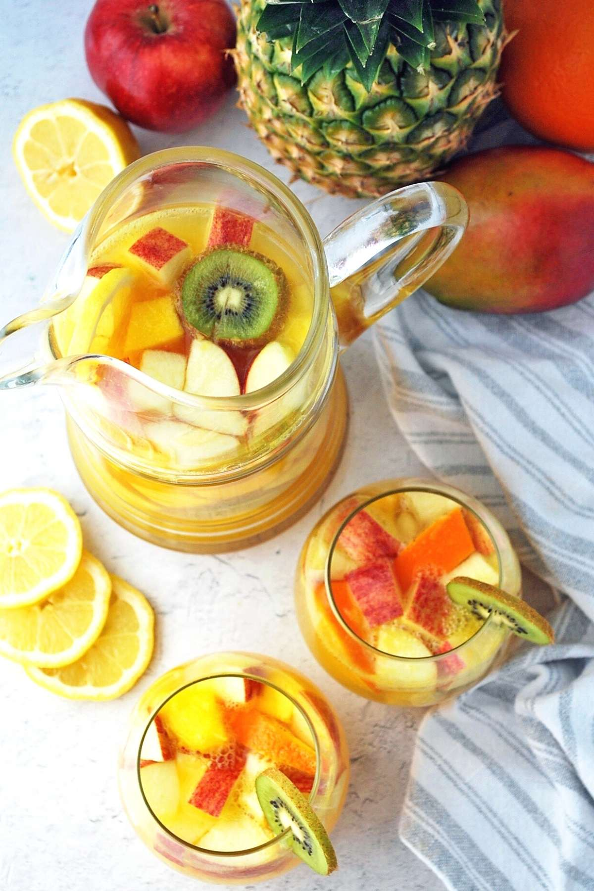Overhead photo of a pitcher of tropical sangria and sangria in glasses surrounded by fruit