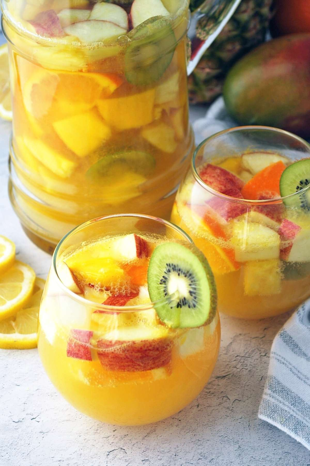 close up of two glasses of tropical sangria garnished with kiwi slices and a pitcher of sangria in the background