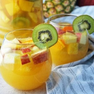 Two glasses of tropical sangria with a pitcher and pineapple in the background
