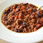 close up photo of chili in a white bowl with a spoon