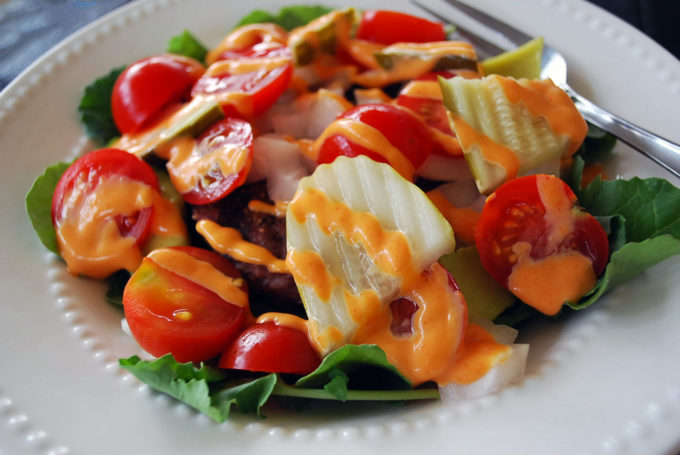 Easy low carb burger salad recipe topped with Sriracha mayo