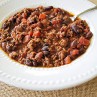Beef chili in a white bowl with a spoon