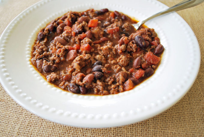 beef chili with beans and tomatoes in a white bowl with a spoon