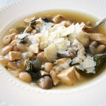 photo of chicken and bean soup with wilted spinach topped with shaved parmesan cheese in a white bowl