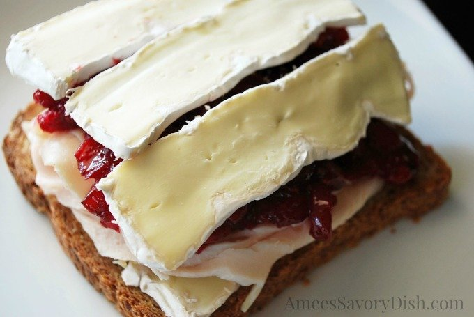 Slices of brie cheese on top of a turkey sandwich with cranberry sauce