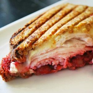 a close up photo of half of a turkey cranberry brie panini on a plate