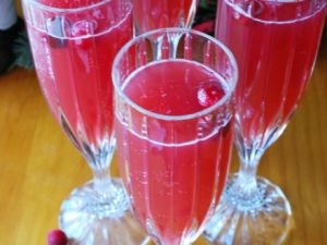 Cranberry Prosecco Cocktail in champagne flutes with berries