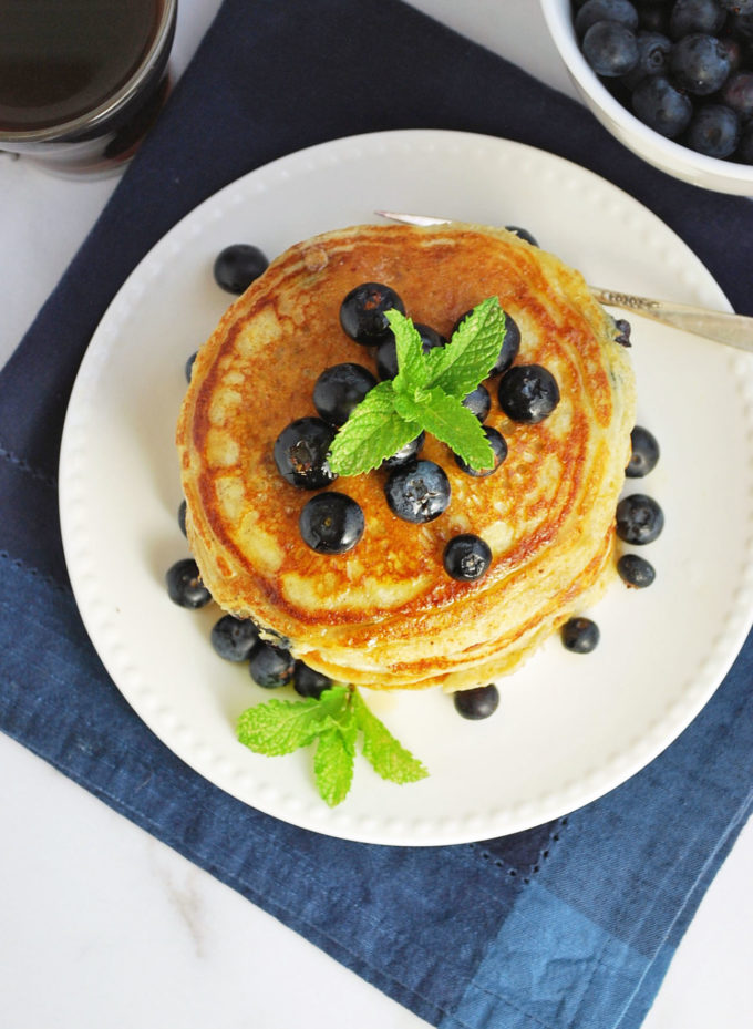 Stack of blueberry protein pancakes with fresh blueberries and syrup on top