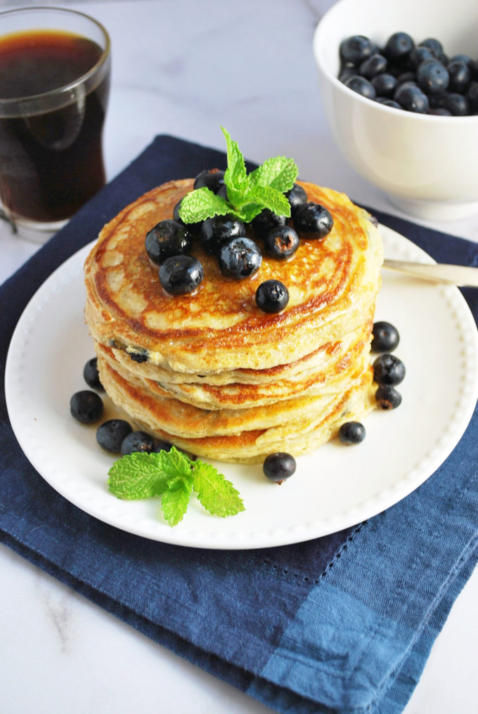 A cup of coffee and bowl of fresh blueberries with a stack of blueberry protein pancakes