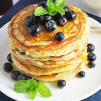 Stack of blueberry pancakes on a plate with fresh berries and mint