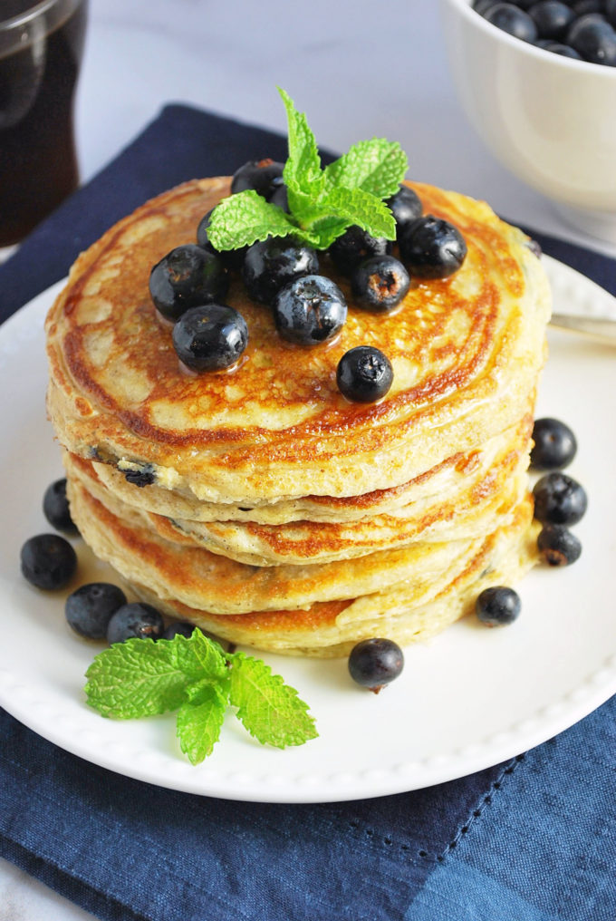 fresh stack of wild blueberry protein pancakes with blueberries on top