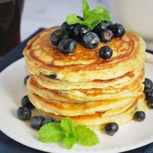 blueberry pancakes stacked on a white plate topped with fresh blueberries, syrup, and fresh mint sprigs