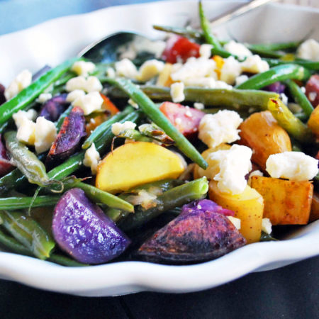 Platter of potato salad with green beans and feta drizzled with lemon dressing