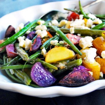 multi-colored fingerling roasted potato salad with green beans and feta cheese in a serving dish