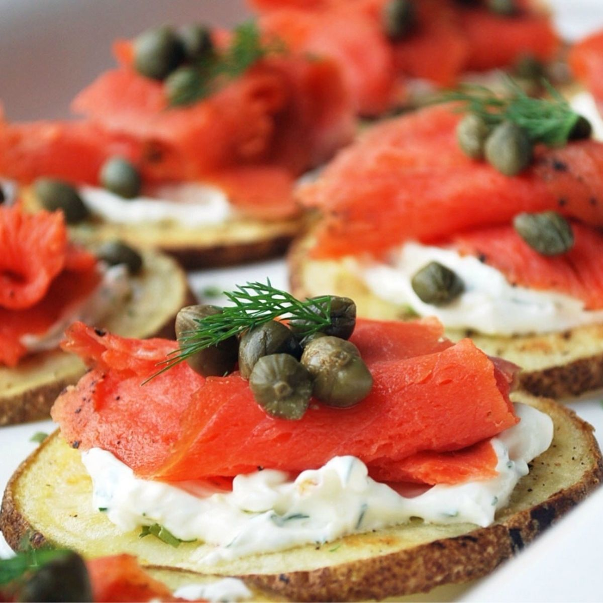close up photo of smoked salmon rounds on a platter with garnish