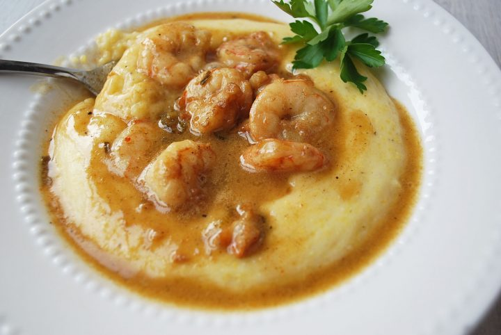 close up shot of shrimp and polenta cheese grits with fresh parsley garnish