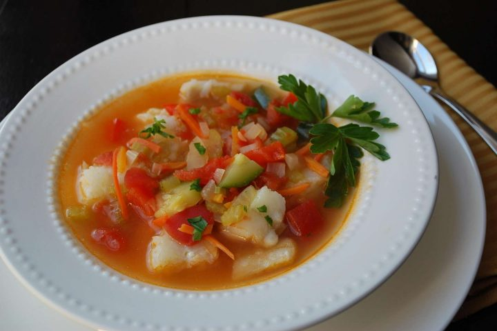 bowl of fish soup with a napkin and a spoon