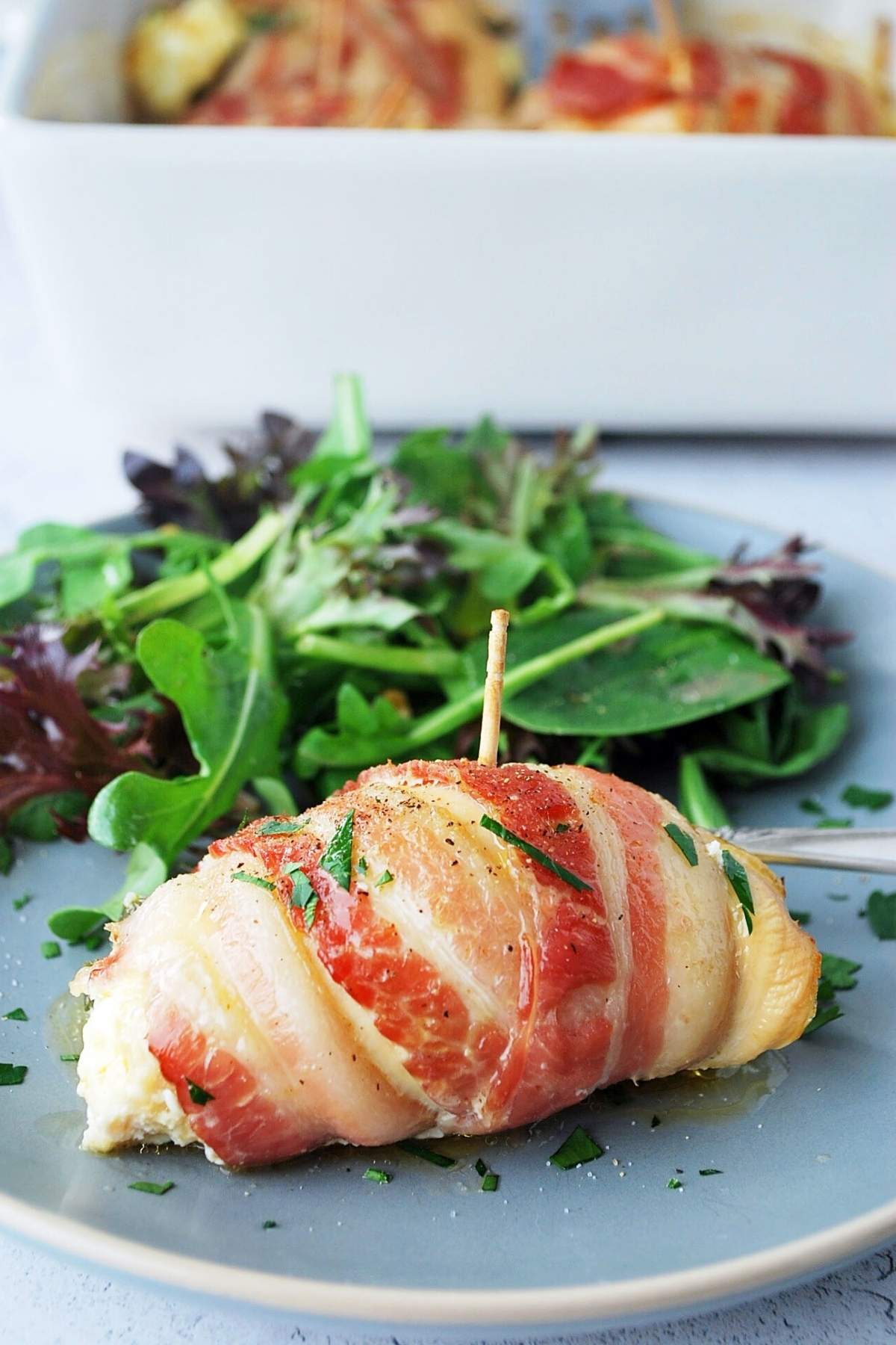 a bacon-wrapped chicken breast on a plate with a side salad and a pan of bacon-wrapped chicken breasts in the background