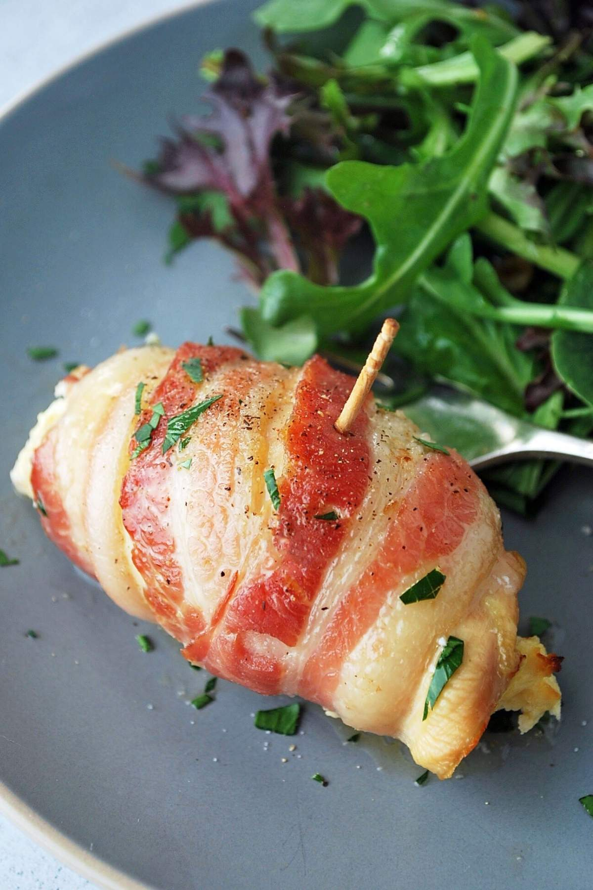 Tex-Mex bacon-wrapped chicken on a plate with salad and a fork