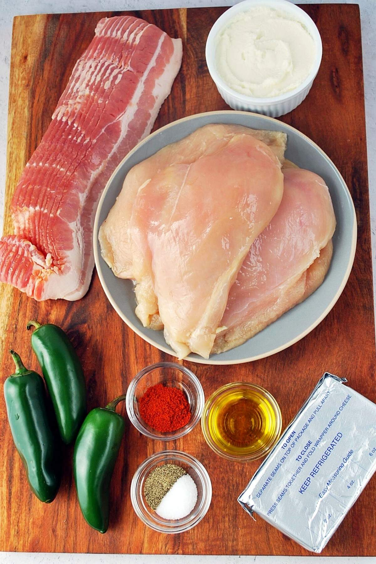 ingredients for bacon-wrapped stuffed chicken on a cutting board