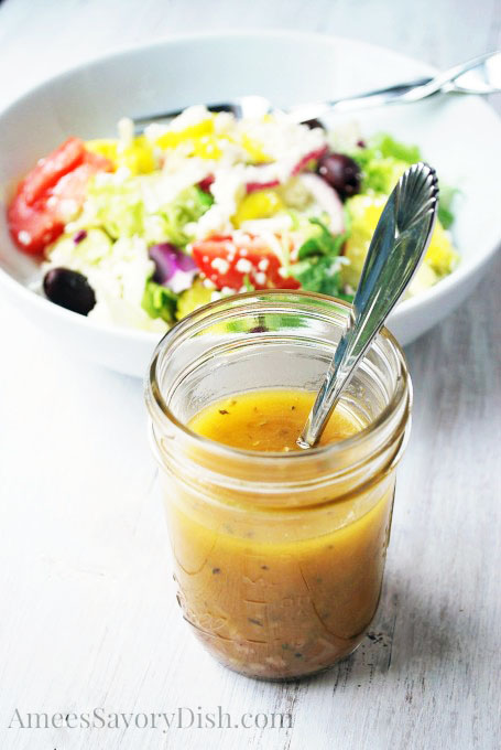 Jar of homemade Greek salad dressing with a spoon and bowl of Greek salad