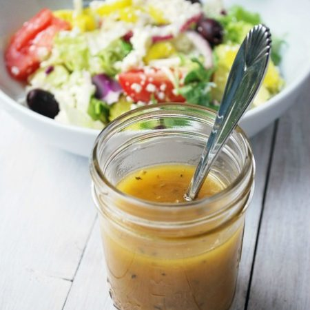 Greek dressing in a mason jar with salad in the background