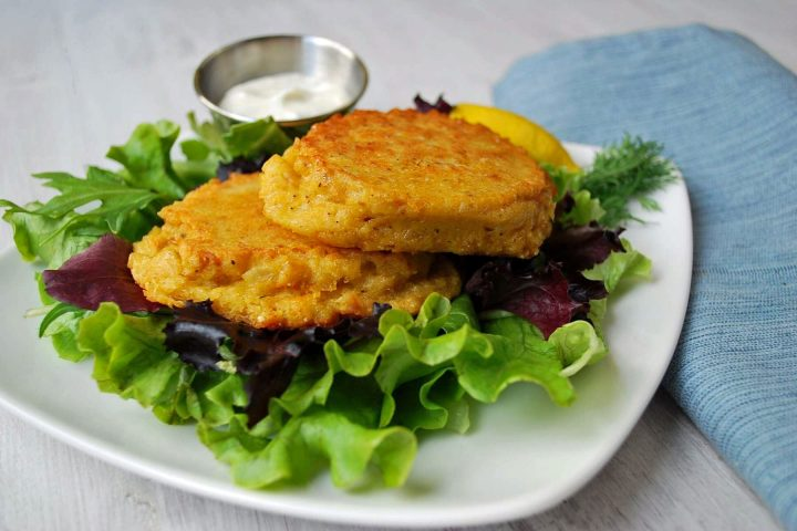 two salmon patties on mixed greens with a dish of yogurt sauce on the side
