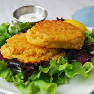 two salmon patties over a bed of greens with a small bowl of sauce on the side