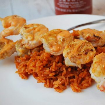 grilled shrimp on skewers over red rice drizzled with Sriracha sauce